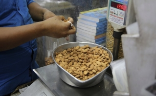 In this June 22, 2019 file photo, a shopkeeper weighs California almonds for a customer at a shop in New Delhi, India. Almonds used to have about 170 calories per serving, then researchers said it was really more like 130. A little later, they said the nuts may have even less. The shifting numbers for almonds show how the figures stamped on nutrition labels may not be as precise as they seem.
