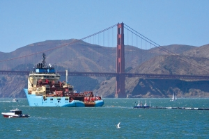In this Sept. 8, 2018 file photo, a ship tows The Ocean Cleanup's first buoyant trash-collecting device toward the Golden Gate Bridge in San Francisco en route to the Pacific Ocean. The floating device designed to catch plastic waste has been redeployed in second attempt to clean up a huge island of trash swirling in the Pacific Ocean between California and Hawaii. Boyan Slat, creator of The Ocean Cleanup project, announced Saturday, June 22, 2019, on Twitter that a 2,000-foot (600-meter) long floating boom that broke apart late last year was sent back to the Great Pacific Garbage Patch this week after four months of repair.