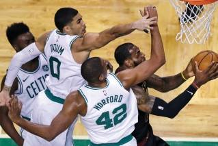 Boston Celtics forwards Jayson Tatum (0) and Al Horford (42) try to stop Cleveland Cavaliers forward LeBron James, right, on a drive to the basket during the first quarter.