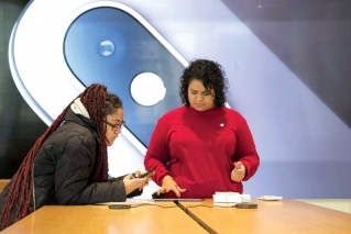 An image of an iPhone is on display in the background as a customer, left, is helped at the Apple store in the Brooklyn borough of New York, Thursday, Jan. 3, 2019. Apple's shock warning that its Chinese sales are weakening ratcheted up concerns about the world's second largest economy and weighed heavily on global stock markets as well as the dollar on Thursday.