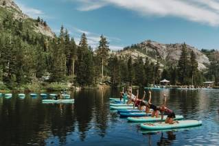 This July 24, 2017 photo provided by Wanderlust, participants work out on paddle boards during Wanderlust Squaw Valley 2017, in North Lake Tahoe, Calif. Wellness tourism is booming, with travelers not just staying fit while on the road, but planning entire trips with a goal of improving their health and well-being.