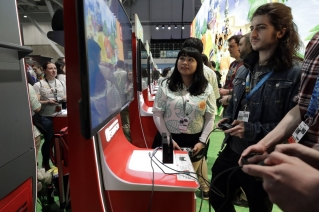 Visitors to the Pax East conference play the new Nintendo Switch video game Animal Crossing, Thursday, Feb. 27, 2020, in Boston. Thousands of gaming enthusiasts attended the Pax East conference that opened in Boston, Thursday.
