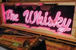 A marquee from the legendary Los Angeles rock 'n' roll club, Whisky a Go Go, glows at the Saco River Auction Co., in Biddeford, Maine.
