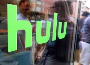 This Saturday, June 27, 2015, file photo, shows the Hulu logo on a window at the Milk Studios space in New York. Hulu will offer a live-streaming service in 2017 that will offer a mix of cable and broadcast programming as well as news, sports and events. That pits the streaming service against similar offerings from Sling TV and PlayStation Vue as more and more Americans shift to watching TV online. (AP File Photo/Dan Goodman)