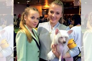 Dog handlers Maren LaPlante, 13, left, and her sister Erin LaPlante, 17, of Caledonia, Wis., pose with Thandy, a Chinese crested, at the Westminster Kennel Club dog show, Monday, Feb. 12, 2018 in New York. Kids as young as 7 have competed there.
