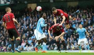 West Bromwich Albion's James Chester, right, climbs over teammate Jonny Evans to win the ball ahead of Manchester City's Wilfried Bony during the English Premier League soccer match at the Etihad Stadium, Manchester, England, Saturday April 9, 2016. (Martin Rickett/PA via AP)